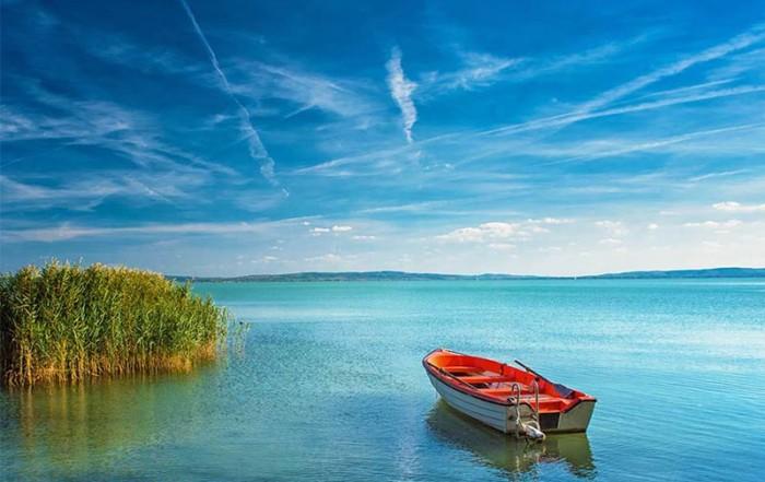 Rotes Fischerboot am tiefblauen Balaton, deutsch Plattensee, in Ungarn, umgeben von grünem Schilf