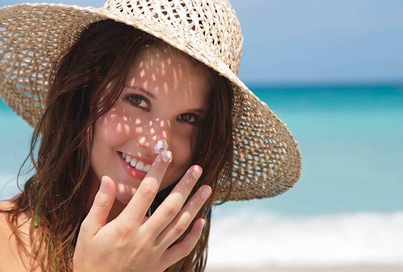 Junges Mädchen schmiert sich Sonnencreme ins Gesicht