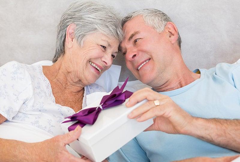 Älteres Pärchen: Mann überreicht seiner Frau ein Geschenk