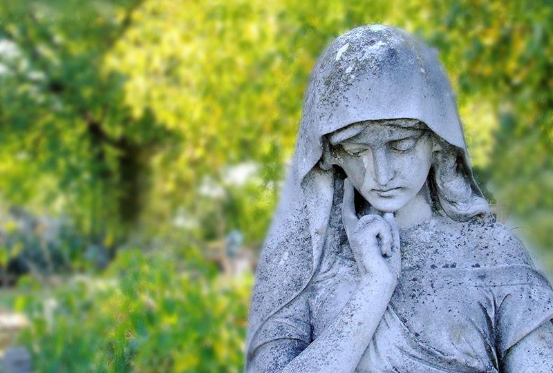 Statue einer weisen Frau mitten im Grünen