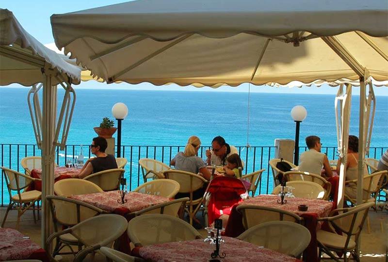 Menschen genießen Eis auf der Terrasse mit Blick auf das türkisblaue Wasser