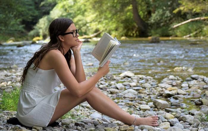 Junge Frau sitzt an einem Fluss und liest ein Buch
