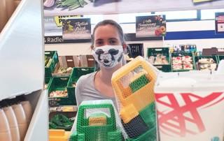 Junge Frau mit kreativem Mund-Nasen-Schutz im Supermarkt