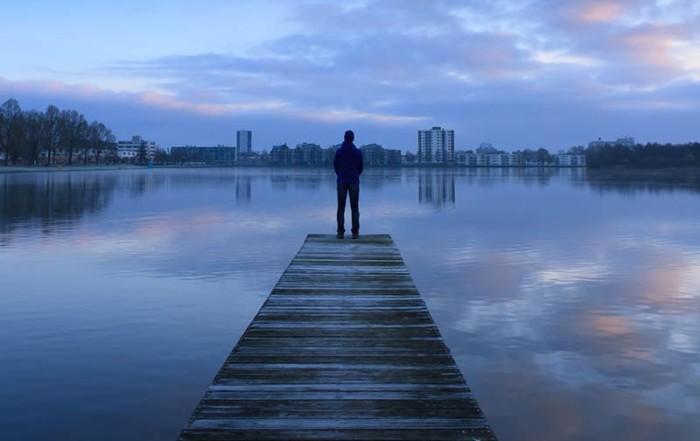 Mann am Bootssteg blickt auf Wasser und Skyline