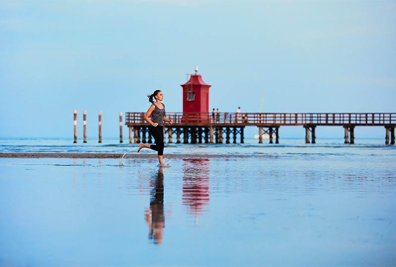 Frau joggt am Strand von Lignano